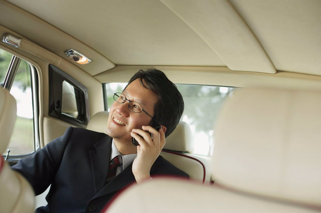 Businessman sitting inside car, using mobile phone : Stock Photo