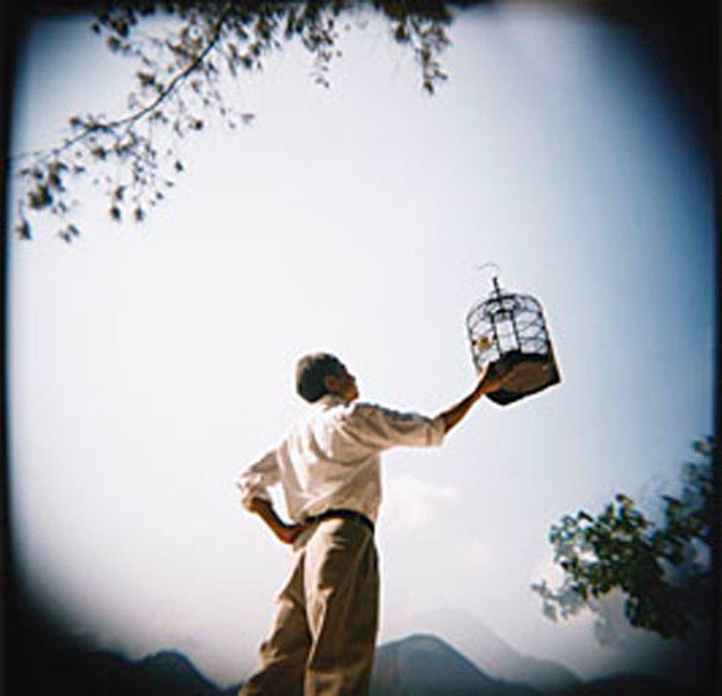 Man holding up birdcage : Stock Photo