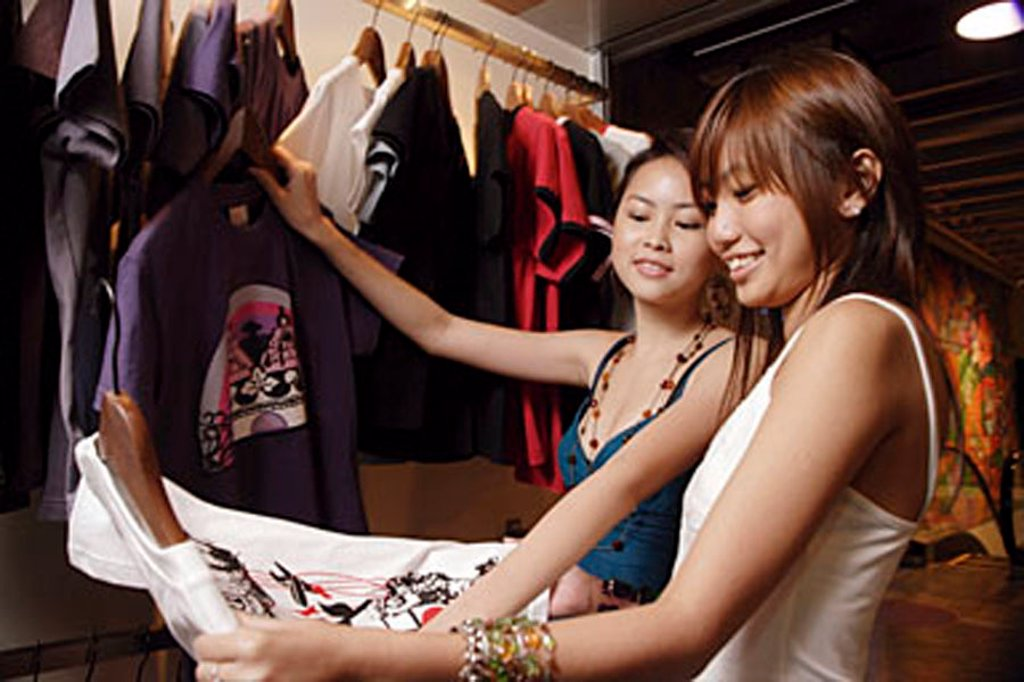 Young women looking at clothes in shop : Stock Photo