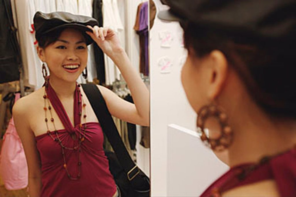 Young woman trying on beret, looking in mirror : Stock Photo