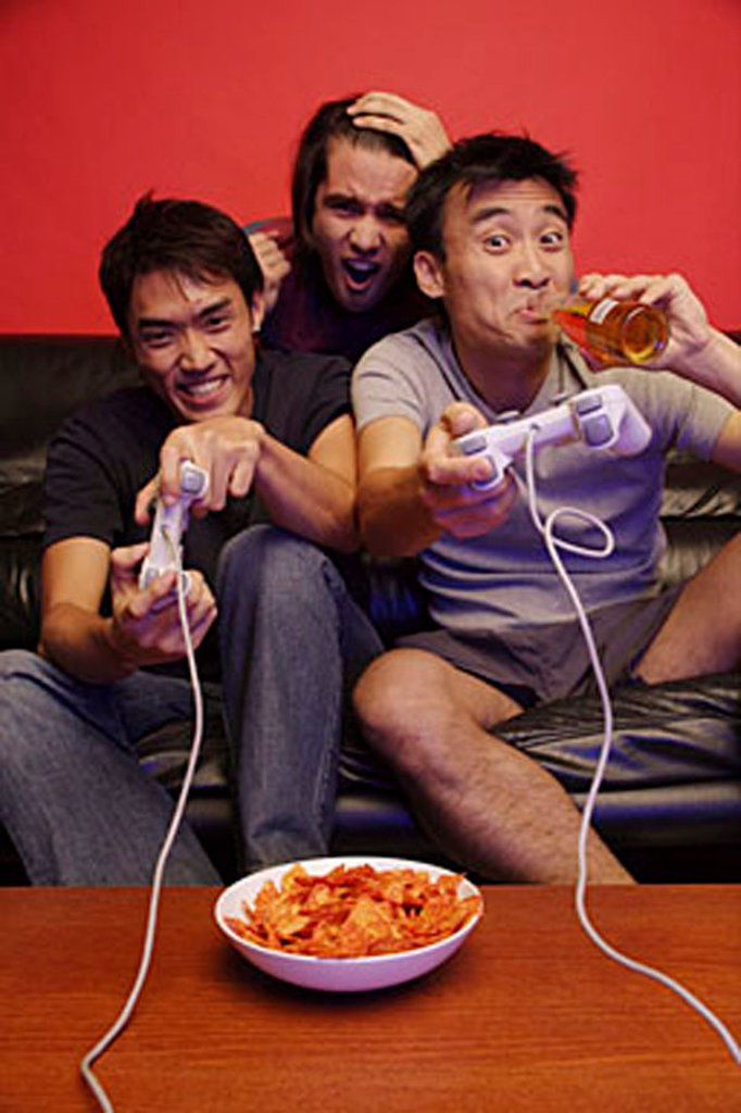Three young men, with video games, beer and chips : Stock Photo