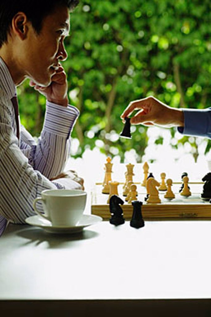 Stock Photo: 4065-2970 Businessmen playing chess, teacup and saucer next to one of them