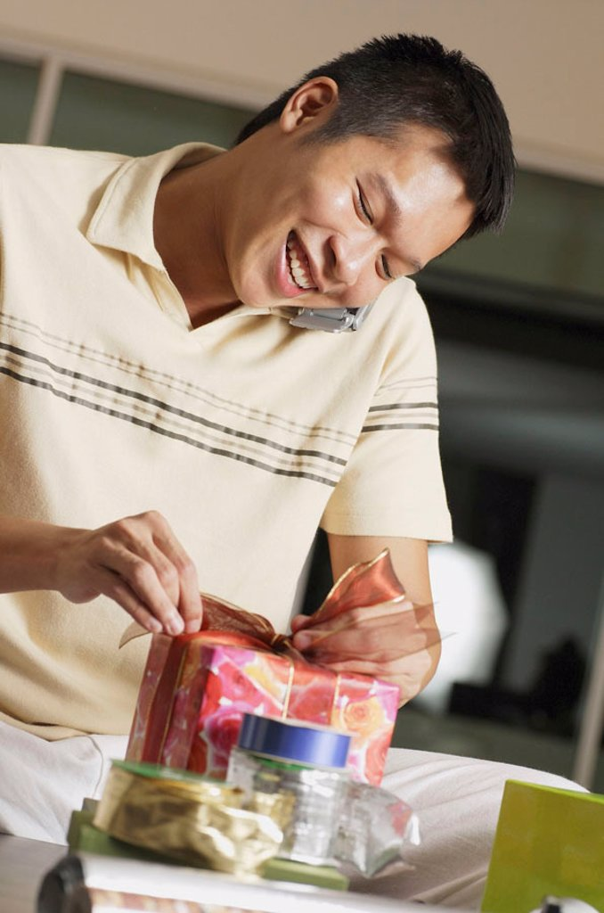Man using mobile phone, opening present : Stock Photo
