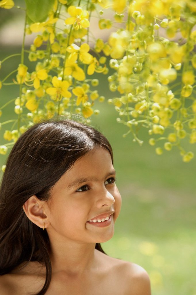 little girl under flowering tree : Stock Photo