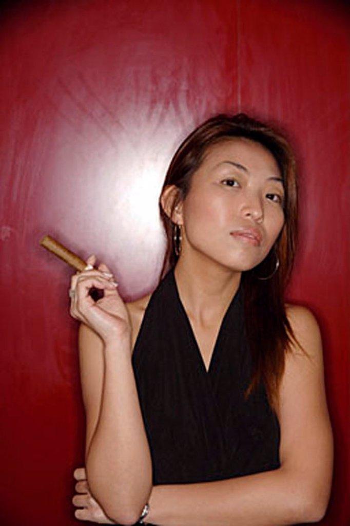 Stock Photo: 4065-3108 Woman with cigar, looking at camera.