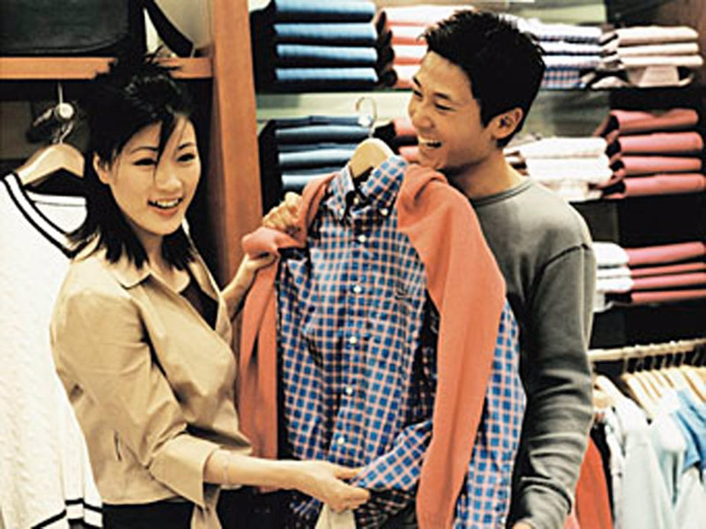 Woman helping man coordinate outfit at clothing store. : Stock Photo