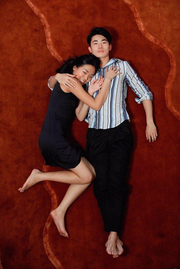 Couple lying on floor, high angle view : Stock Photo