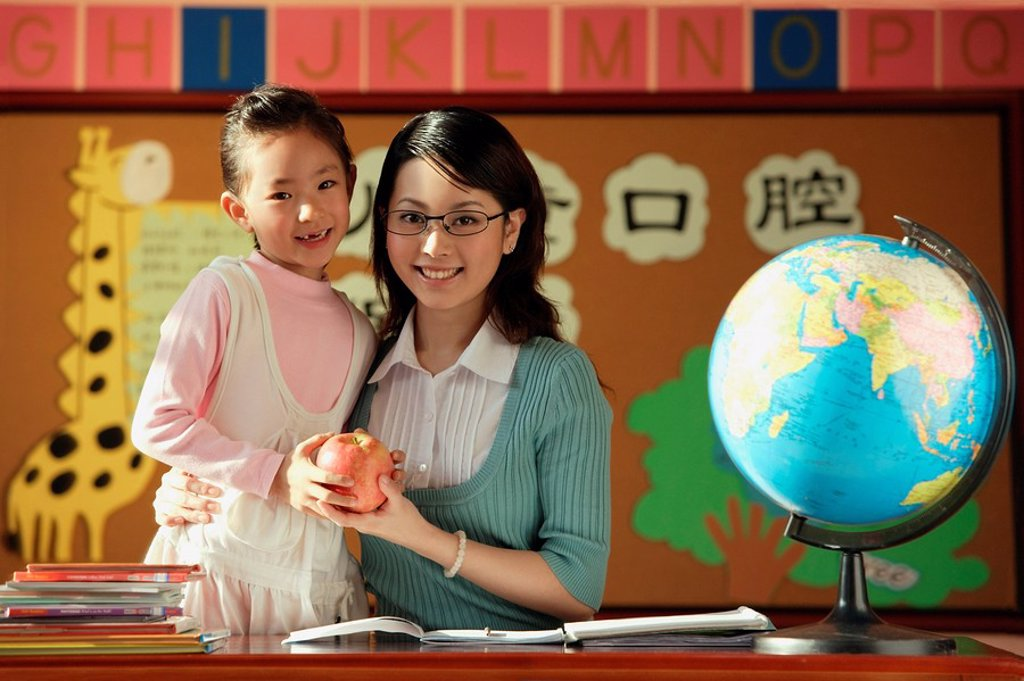 Young student giving teacher an apple : Stock Photo