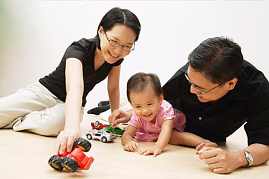 Stock Photo: 4065-3696 Father, mother and daughter playing with cars