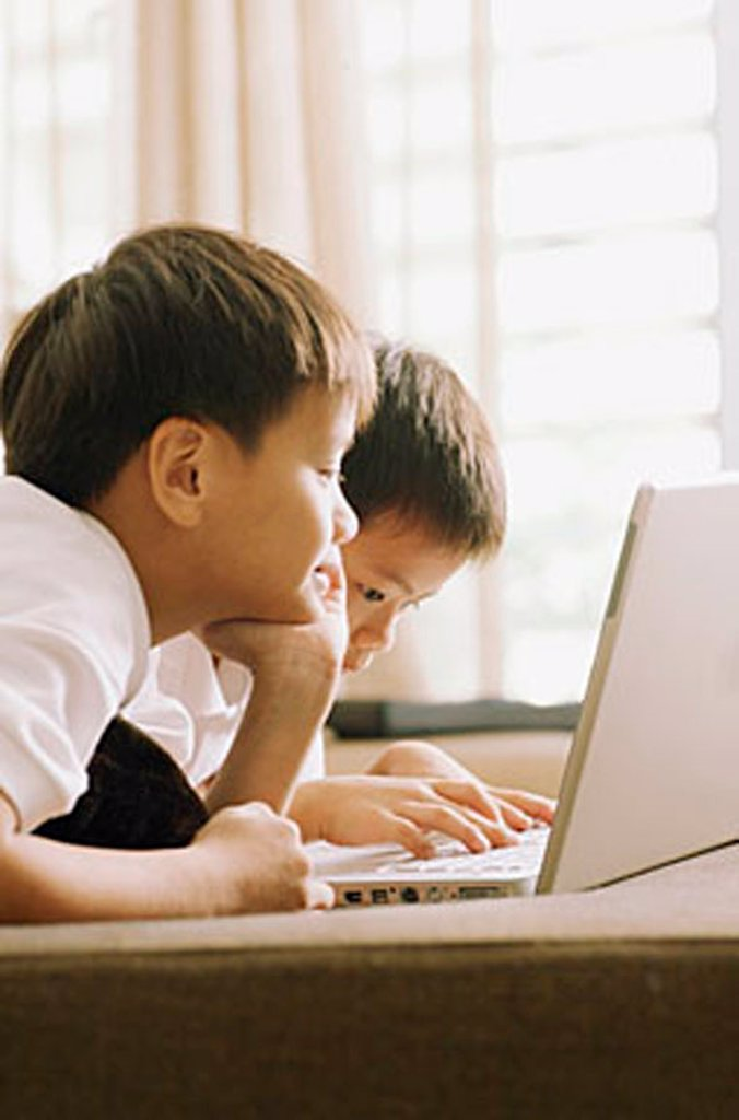 Two children using laptop, side by side : Stock Photo