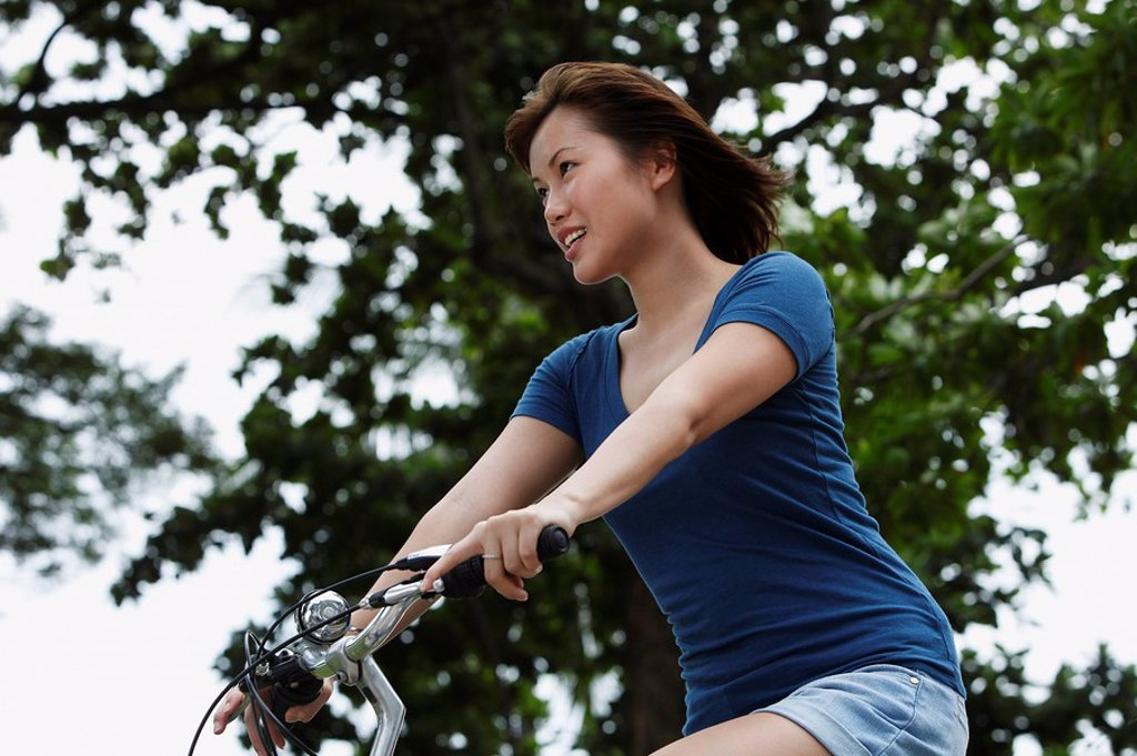 Young woman riding bike : Stock Photo