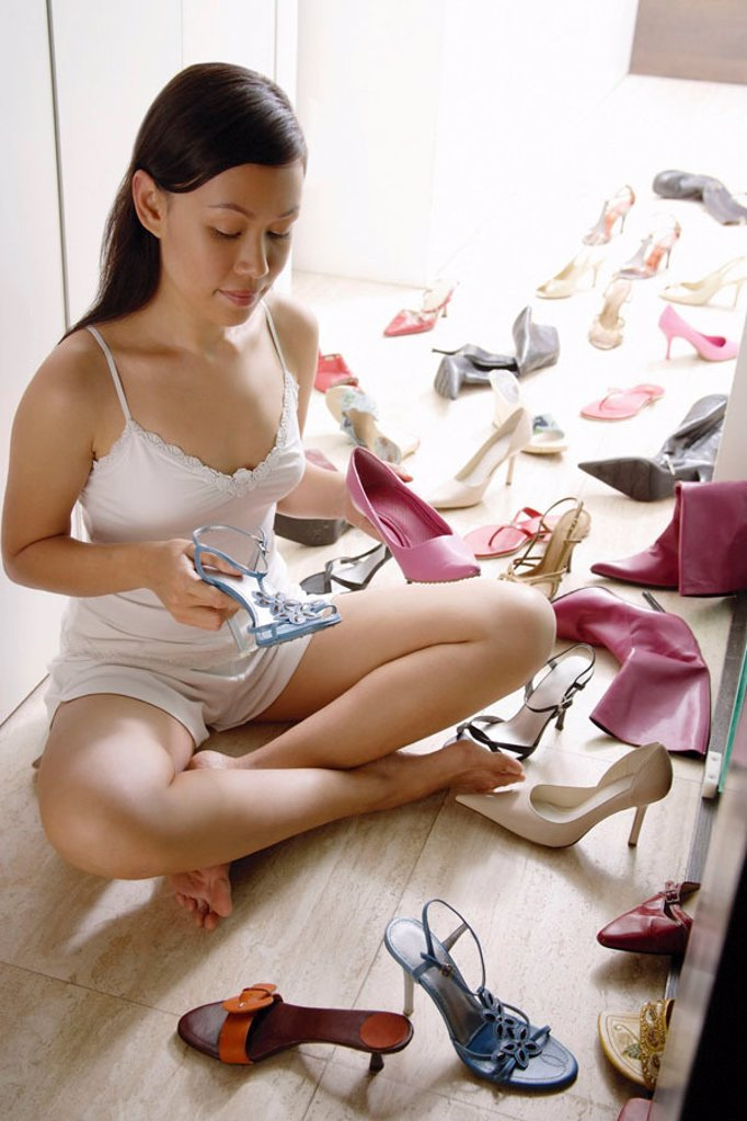 Woman at home, sitting cross legged on floor, surrounded by shoes : Stock Photo