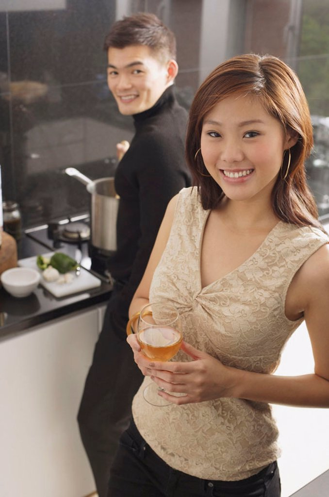 Stock Photo: 4065-5388 Couple in kitchen, man cooking at stove, woman holding wine glass
