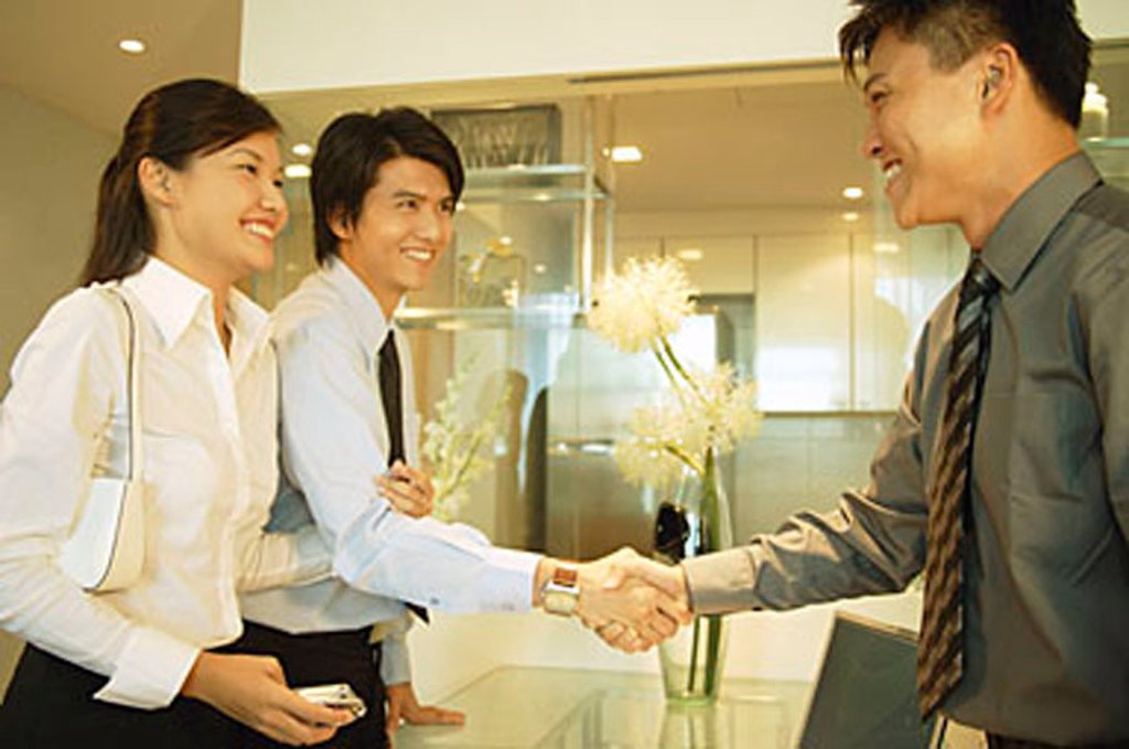 Two businessmen shaking hands, woman holding the arm of one of them : Stock Photo