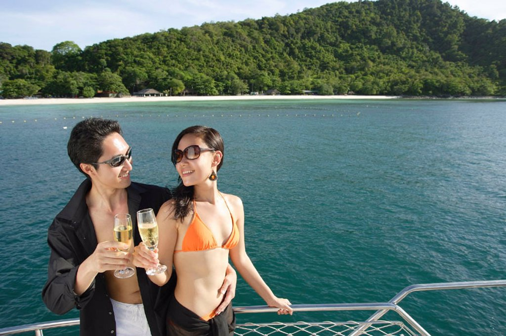 Stock Photo: 4065-5712 Couple on boat deck, standing next to railing, toasting champagne glasses