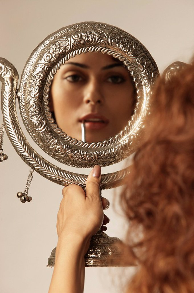 Stock Photo: 4065-5782 Young woman painting her lips, using hand mirror