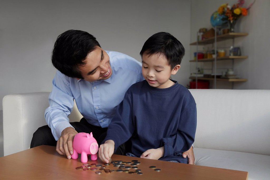 Father talking to young son about finances : Stock Photo