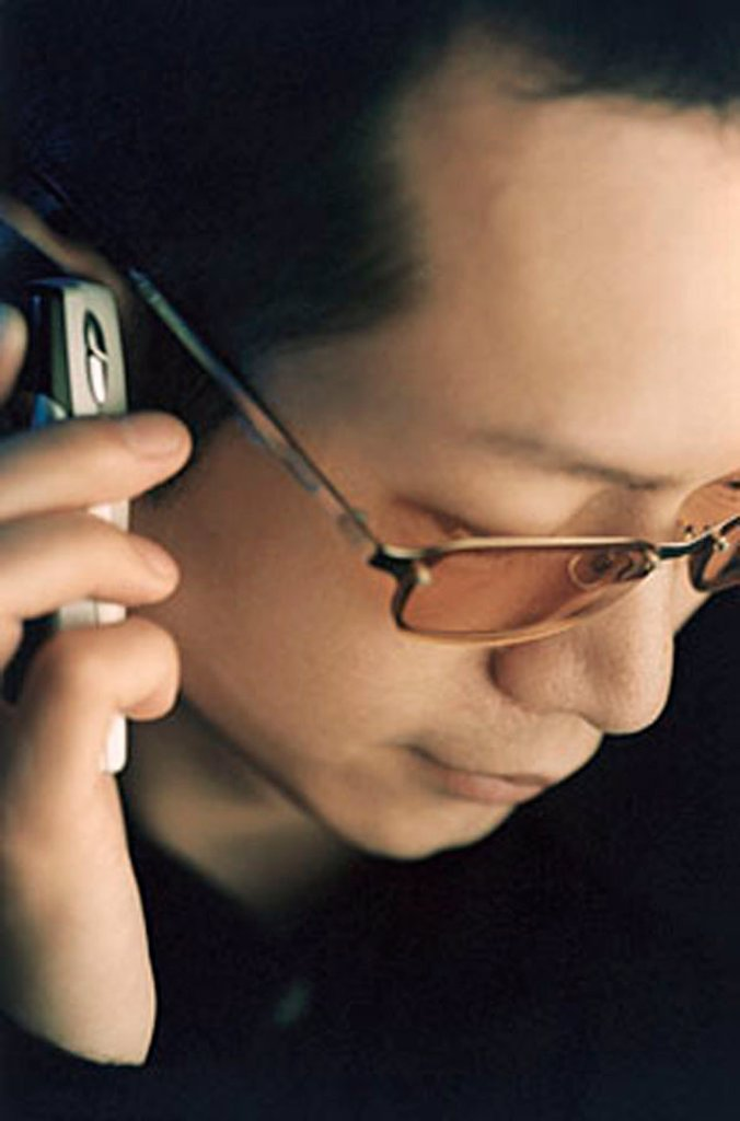 Stock Photo: 4065-5814 Man wearing glasses using cellular phone, looking down