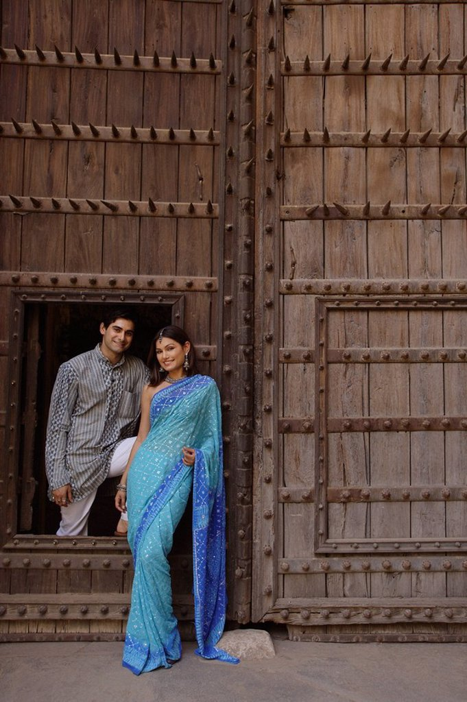 young couple posing at wooden doorway : Stock Photo