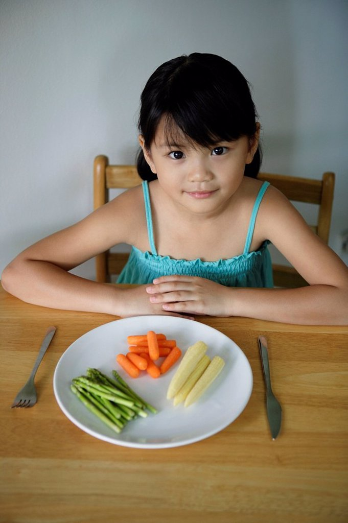 Little girl with plate of vegetables : Stock Photo