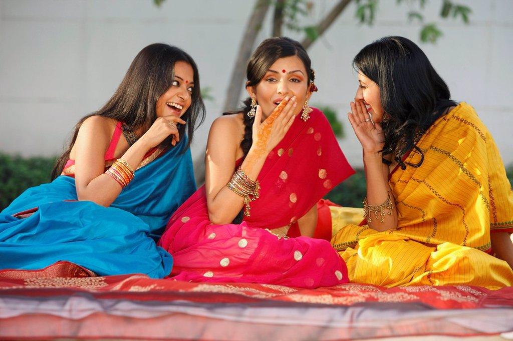 three women in saris, gossiping : Stock Photo