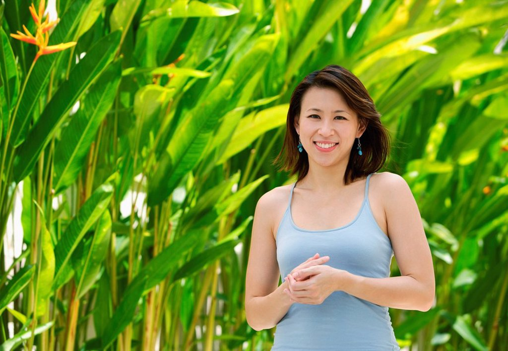 Stock Photo: 4065-6319 Woman standing outdoors, smiling at camera