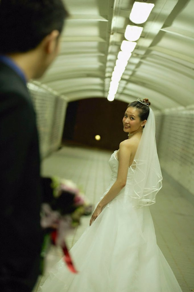 Bride and groom walking in tunnel, bride turning to look at groom : Stock Photo
