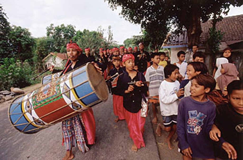 Indonesia, Lombok, Drummers leading a wedding procession past a crowd on the street. : Stock Photo