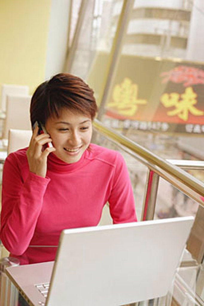 Young woman using laptop and mobile phone : Stock Photo