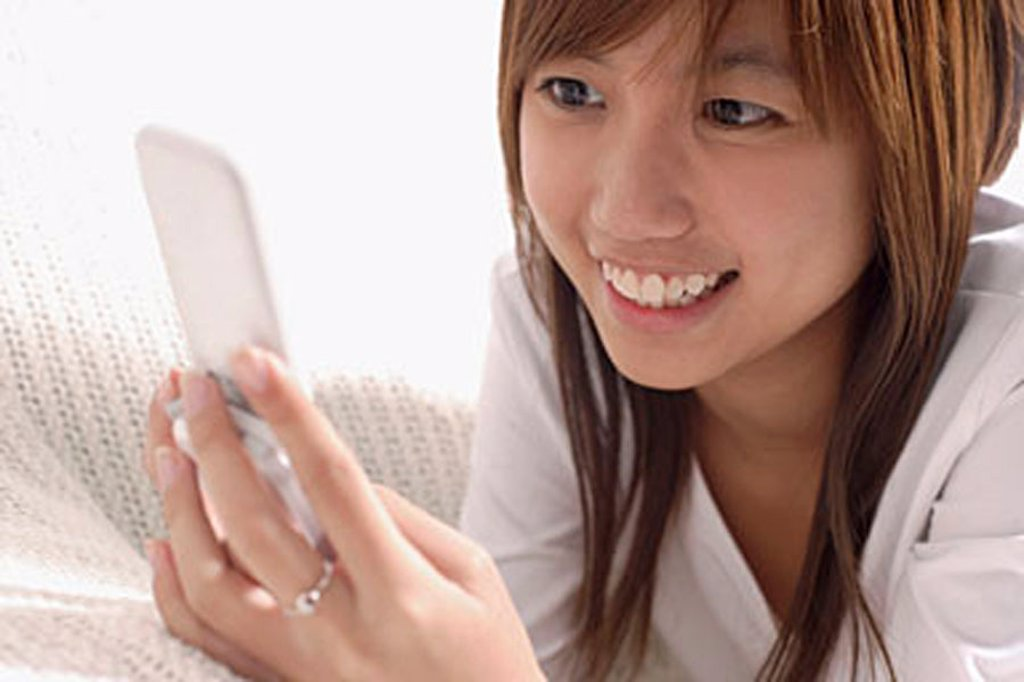Young woman using mobile phone, text messaging : Stock Photo