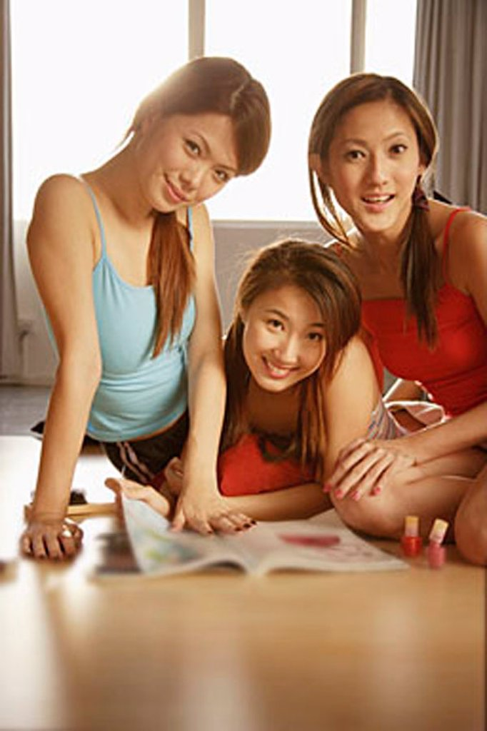 Stock Photo: 4065-7193 Young women looking at camera, magazine open in front of them