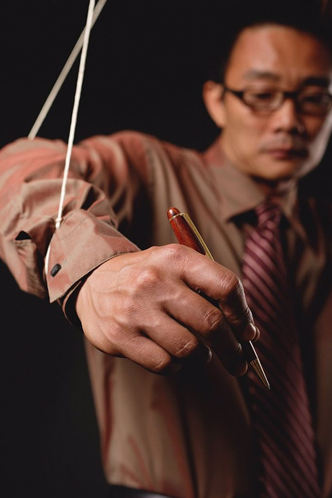 Man with marionette strings attached to his hands, holding pen : Stock Photo
