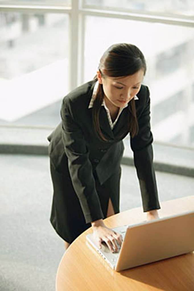 Young woman standing, using laptop : Stock Photo