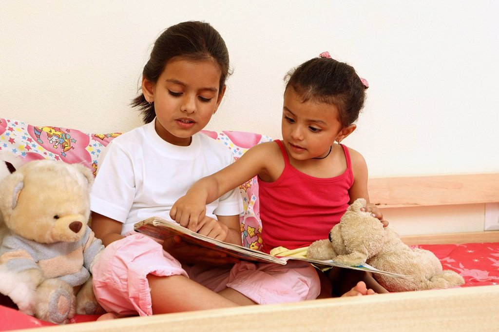 Sisters reading story book : Stock Photo