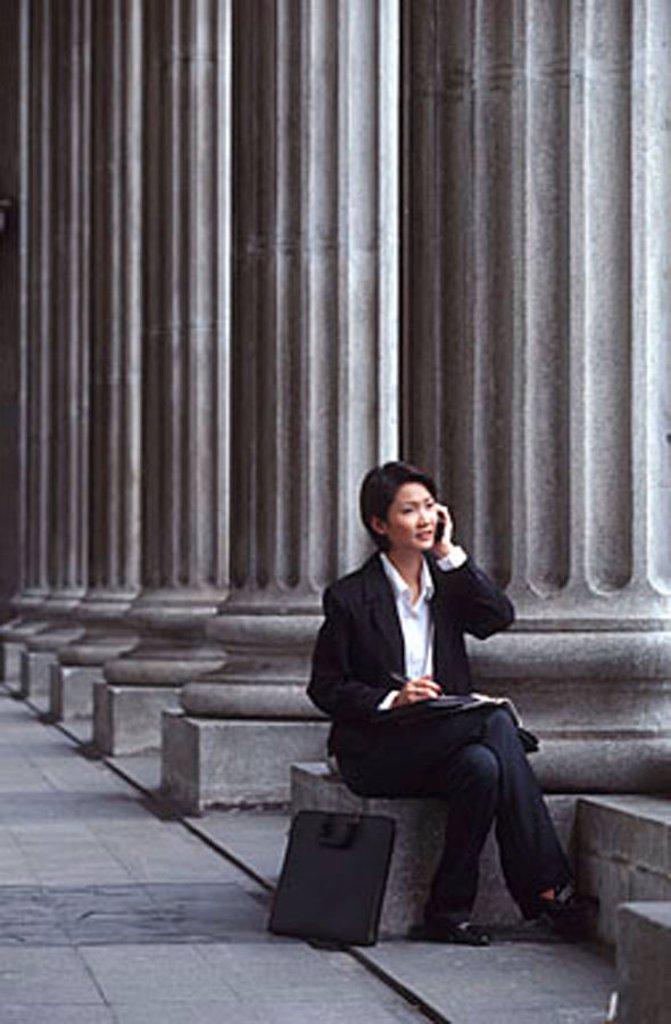 Stock Photo: 4065-7775 Female executive sitting, using cellular phone