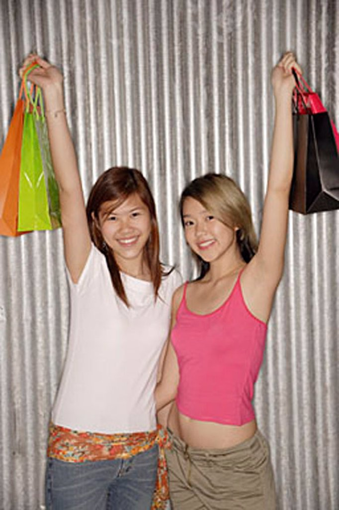 Young women holding shopping bags looking at camera : Stock Photo
