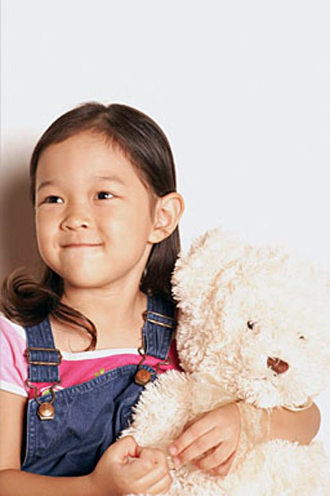 Young girl holding teddy bear, looking away : Stock Photo