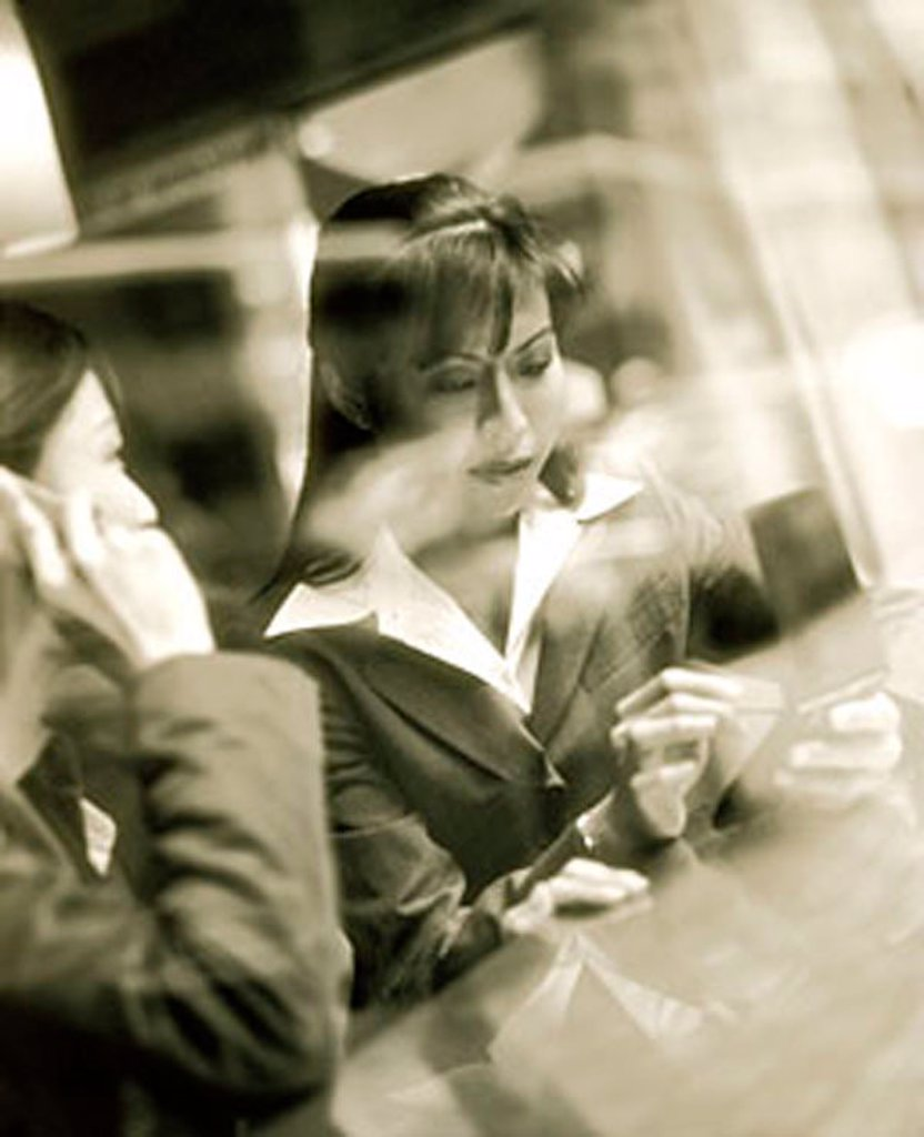 Stock Photo: 4065-8097 Female executives using PDA and cellular phone seen through glass window.