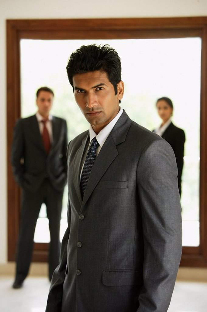 Stock Photo: 4065-8230 businessman in foreground, two business associates in background