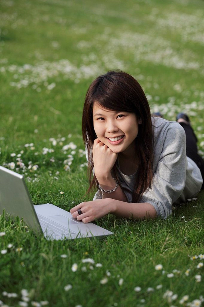 Stock Photo: 4065-8246 Chinese woman laying on grass with laptop.