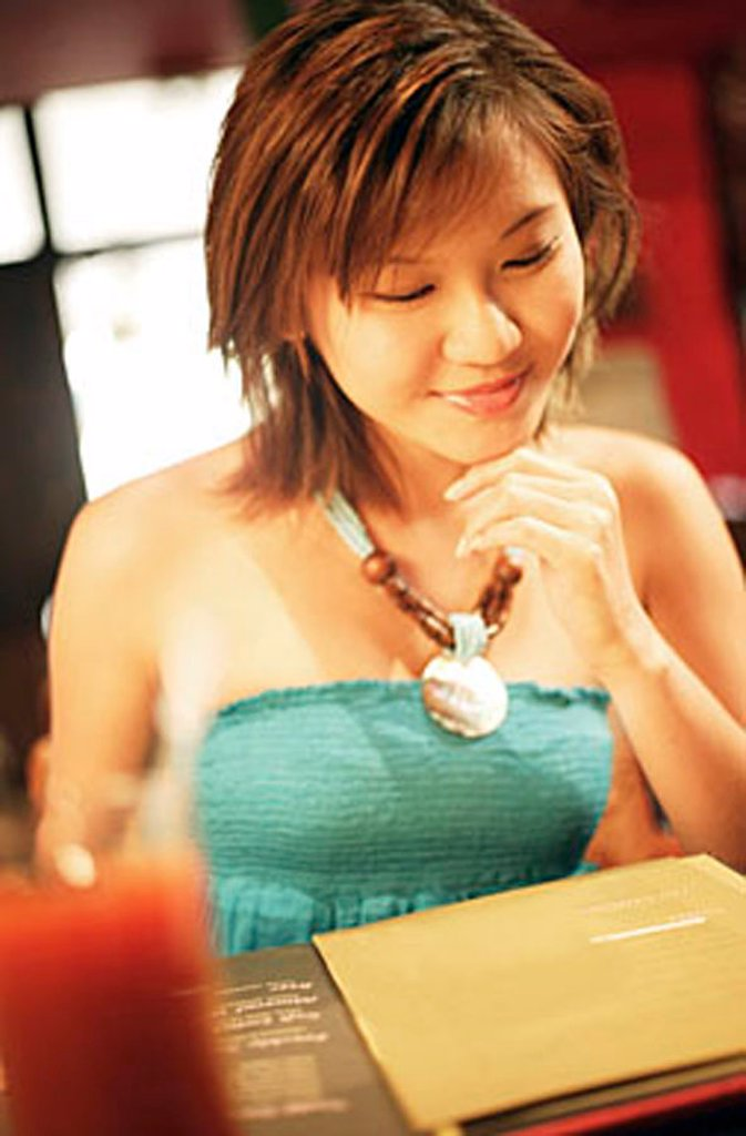 Young woman with hand on chin, looking down at menu : Stock Photo