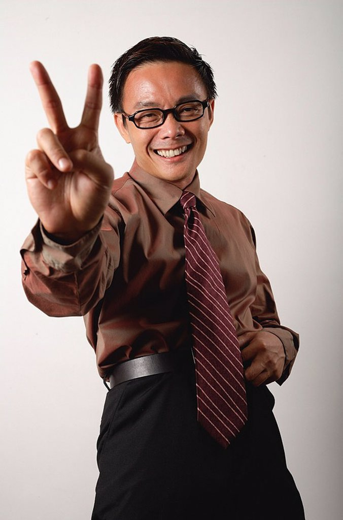 Nerdy businessman making peace hand sign : Stock Photo