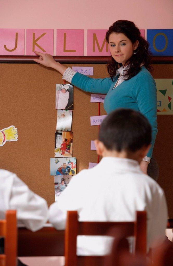Teacher teaching alphabet in class : Stock Photo
