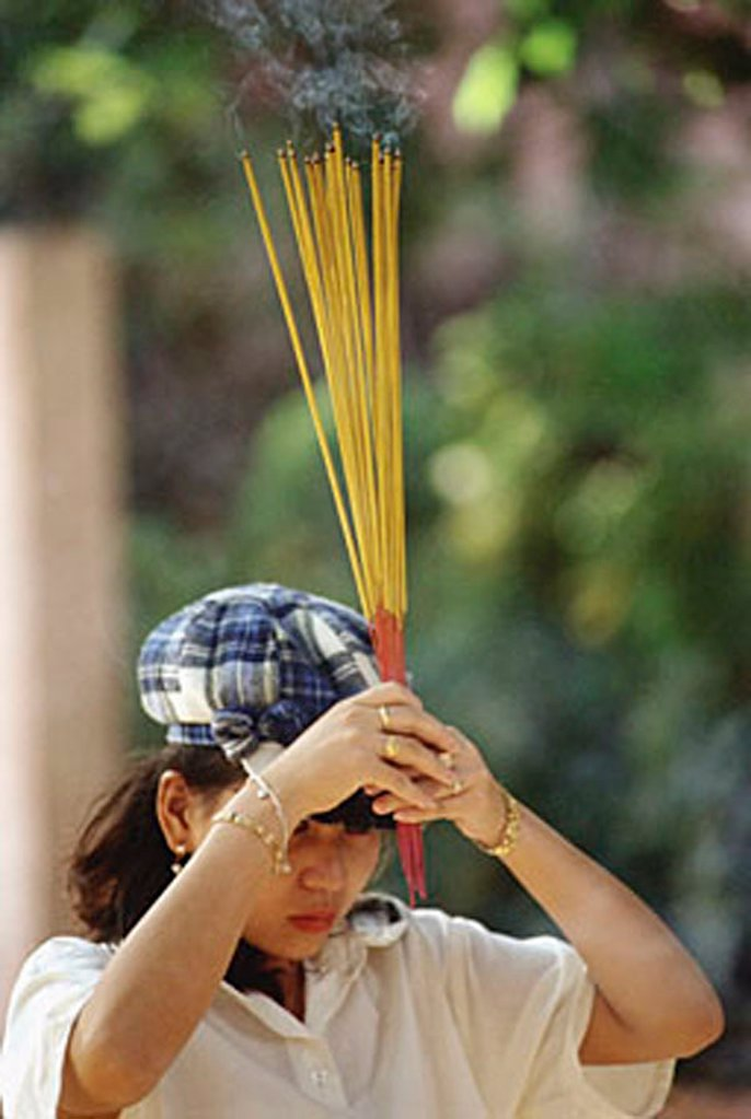 Vietnam, Ho Chi Minh City, A woman waving incense sticks during prayer. : Stock Photo