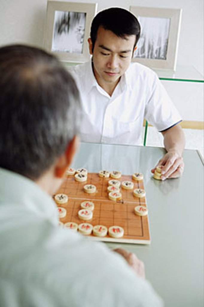 Young man playing Chinese chess with older man : Stock Photo