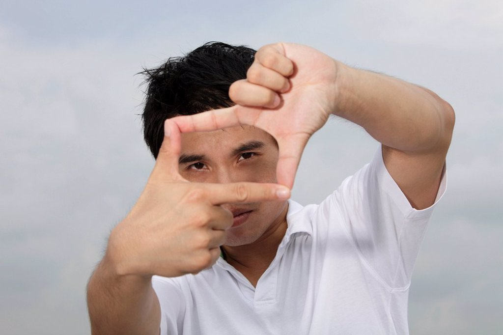 Stock Photo: 4065-9505 Asian man looking through finger frame