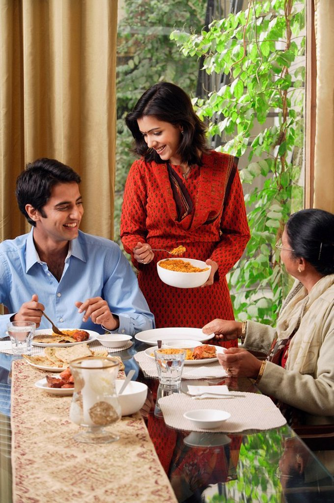 Stock Photo: 4065-9657 woman serves dinner to man and older woman vertical