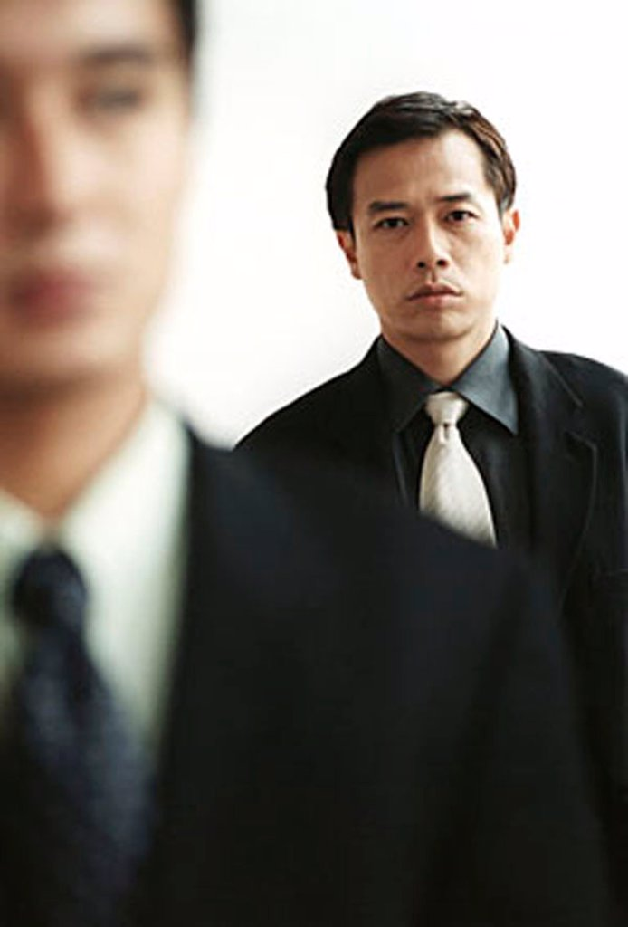 Two male executives, one out of focus in foreground. : Stock Photo