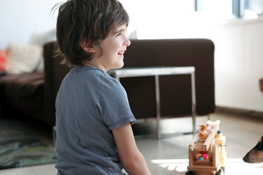 Boy playing in a living room : Stock Photo