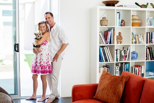 Mature couple with dog standing in doorway of home : Stock Photo
